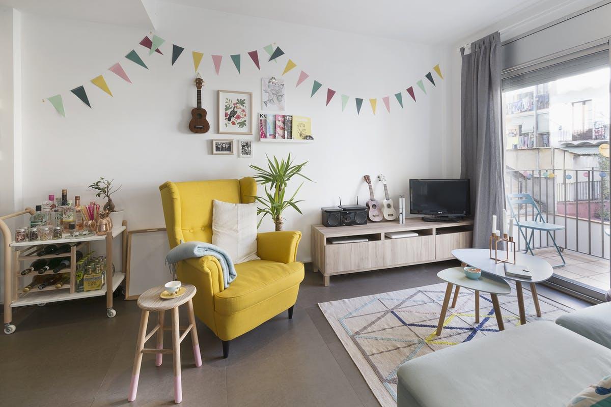 Salon z fotelem szafką pod telewizor, dywanem i barkiem na kółkach z IKEA